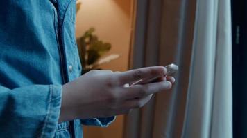 garota em pé digitando em um smartphone em frente à janela foto