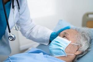 médico ajuda paciente idoso asiático usando máscara para proteger o coronavírus foto