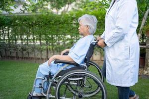 médico ajuda paciente idosa asiática sentada em cadeira de rodas no parque foto