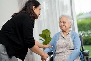 ajuda e cuidados paciente mulher asiática sentada em uma cadeira de rodas foto