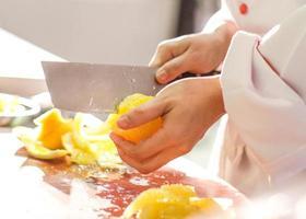 casca de limão, chef cortando limão, fatiando limão na tábua foto