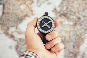 mão de homem segurando uma bússola vintage com mapa-múndi como pano de fundo foto
