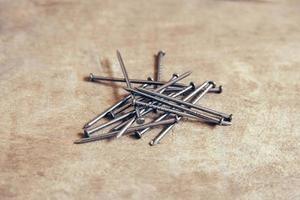 pilha de pregos de metal em fundo de madeira foto