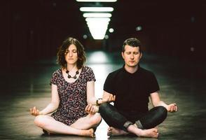 jovem casal meditando juntos sentado no estacionamento foto