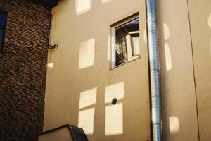 parede de concreto amarela com janela aberta e reflexos de vidro foto