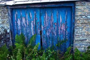 porta de casa de madeira velha com pilares de pedra foto