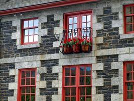 janelas vermelhas e belos edifícios de pedra foto