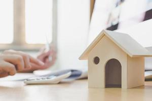 modelo doméstico de madeira e casa chave na mesa de madeira foto