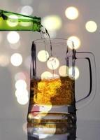 derramando cerveja em um copo com iluminação especial desfocar o fundo foto
