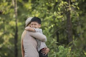 retrato de mãe e filho feliz se abraçando no parque. foto