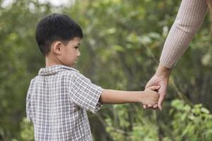 perto de feliz mãe e filho segurando a mão em um parque. conceito de família. foto