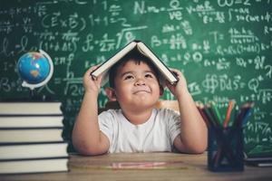 menino pensativo com livro na sala de aula foto