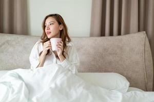 retrato de mulher bonita acordar e segurando uma xícara de café ou caneca na cama foto
