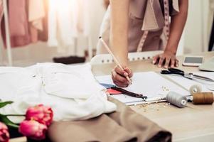 closeup da mão do estilista feminino trabalhando em um escritório em casa foto