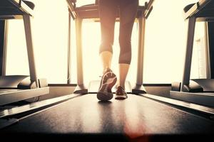 parte inferior do corpo na parte das pernas da garota fitness correndo na máquina de corrida foto