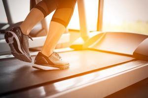 parte inferior do corpo na parte das pernas da garota fitness correndo na esteira foto