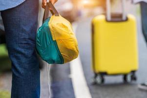 closeup de pernas de turista caminhando ao longo da estrada com uma bolsa durante a viagem foto