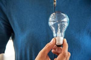 lâmpada na mão da mulher. ideia e conceito criativo foto