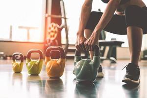 close-up de uma mulher levantando halteres de kettlebell no clube de esporte fitness foto