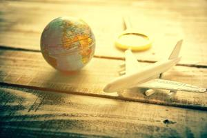 pequeno avião e globo e lentes de aumento na mesa de madeira foto