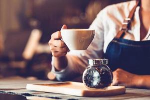 closeup da mão feminina de barista fazendo e segurando uma xícara de café foto