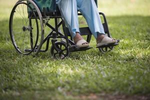 close-up idosa solitária sentada em uma cadeira de rodas no jardim foto