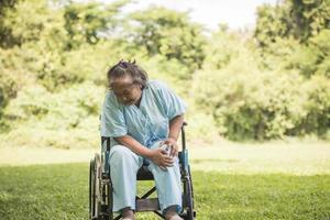 mulher idosa sentada em cadeiras de rodas com dor no joelho foto