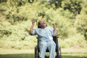 idosa solitária sentada em uma cadeira de rodas no jardim de um hospital foto
