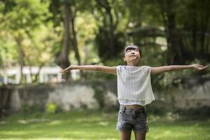menina feliz mostra a mão no ar no jardim foto