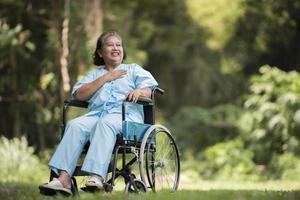 idosa solitária sentada, sentindo-se triste em uma cadeira de rodas no jardim foto
