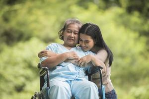 neta conversando com a avó sentada na cadeira de rodas foto