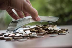 economizando o conceito de dinheiro. mão colocando dinheiro pilha de moedas foto