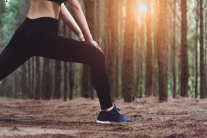 close-up da parte inferior do corpo de uma mulher fazendo ioga e esticando as pernas foto