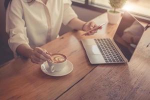 close-up de mulher de negócios trabalhando com laptop e bebendo café foto