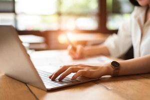 close-up de uma mulher digitando o teclado no laptop na cafeteria foto