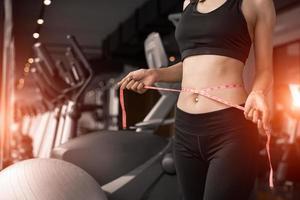 mulher desportiva usando fita adesiva na cintura no treinamento do clube de esporte de ginásio foto