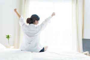 vista traseira de mulher se alongando pela manhã após acordar foto