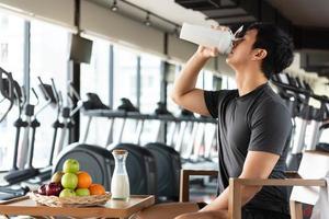 homem bonito bebendo leite batido de proteína e muitos tipos de frutas foto