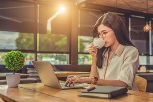Mulher asiática que trabalha usando laptop e tomando café no café foto