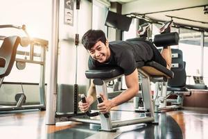 homem esporte asiático alongando e levantando peso com as duas pernas foto