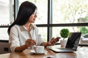 mulher de negócios trabalhando com laptop e smartphone e bebendo café foto