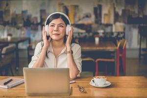 mulher asiática feliz relaxando e ouvindo música em uma cafeteria foto