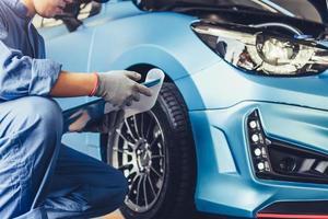 Técnico de mecânico de automóveis asiático segurando a prancheta, verificando a manutenção foto