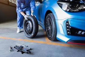 mecânico de automóveis trocando pneu em oficina mecânica foto