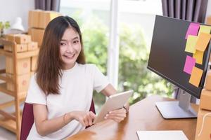 Mulher asiática usando tablet com caixas de pacote no tema serviço de entrega foto