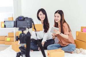 duas mulheres asiáticas usando uma câmera de vídeo digital para gravar foto