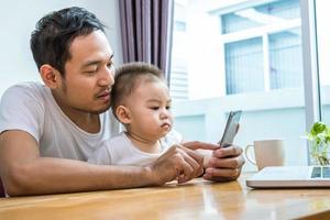pai e filho asiáticos usando telefone inteligente juntos em casa foto