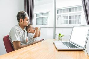 pai e filho asiáticos usando smartphone e laptop juntos em casa foto