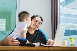 filho beijando o pai enquanto usa a internet. pessoas e estilos de vida foto