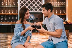 casais jovens asiáticos tilintando taças de vinho em bar doméstico foto